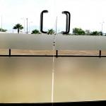 Pegatina Esmerilada sobre Cristal Templado En fábrica del vinil te ofrecemos Pegatina Esmerilada de máxima calidad, con una duración de 4 a 6 años. Este tipo de material translucido es ideal para evitar el paso excesivo de luz en oficinas, dividir espacios y crear privacidad. Es posible instalarlo sobre cualquier cristal, incluyendo el cristal templado, con métodos secos o húmedos. Vendemos vinilo esmerilado sin diseño (liso) o con cualquier tipo de silueta cortada. Puedes combinarlo con otros colores brillantes y opacos para formar figuras más complejas y que respondan tu gusto. Este material es prácticamente permanente (debido a que usamos materiales especializados de la mejor calidad) y a la vez es posible removerlo, de tal forma que no dañe en absoluto la superficie del cristal. La instalación de este proyecto fue la solución al exceso de luz que a ciertas horas del día inundaba la recepción de la empresa, esto hacía imposible ver los monitores de las computadoras sin contar las molestias de la recepcionista y los clientes al ser atendidos. A diferencia de la mayoría de tiendas de vinilos en línea, que solamente son distribuidores de diseños prefabricados y además no instalan los mismos. Fabrica del vinil surgió como respuesta a la necesidad de nuestros clientes por encontrar un servicio integral de diseño, corte e instalación de vinilos, para las más diversas aplicaciones. Puedes fácilmente contactarnos por varios medios electrónicos y recibir tus vinilos en cualquier parte del país, ya que hacemos envíos desde Guadalajara Jalisco a todo México. Algunas de las ventajas de nuestro vinil cortado son: Material Norteamericano especializado Durable a la intemperie de 4 a 6 años Colores solidos súper vivos (mucho más que el vinil impreso) Gran precisión en los trazos (imposibles de lograr a mano) Tenemos disponibles materiales especiales (sobre pedido) Manejamos una amplia paleta de colores Poderoso adhesivo de gran calidad Es un material de fácil aplicación No daña 